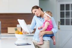 Frauenlesedokumente beim Tragen des Babys Stockfotografie
