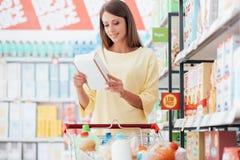 Frauenleselebensmittelkennzeichnungen stockfotografie