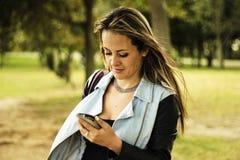 Frauenlesenachrichten auf einem Mobiltelefon stockbilder
