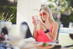 Frauenlesetextnachricht auf Mobile Stockbild