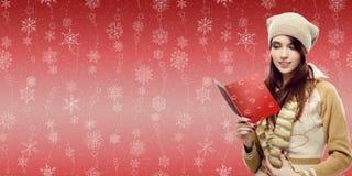 Frauenleseweihnachtspostkarte über Winterschneeflocken backgrou Stockfotos