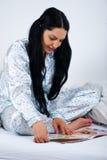 Frauenlesezeitschrift im Bett Stockbild