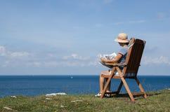 Frauenlesezeitung in einem Stuhl mit schöner Ansicht Stockbild