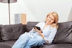Frauenlesung auf einer Tablette Stockbild
