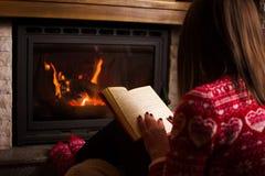 Frauenlesung durch den Kamin lizenzfreies stockfoto