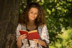 Frauenlesung durch einen Baum Stockfoto