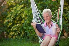 Frauenlesung im Ruhestand lizenzfreie stockfotografie