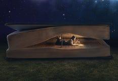 Frauenlesung innerhalb eines enormen Buches Stockfoto