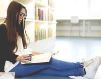 Frauenlesung mit Tasse Kaffee Lizenzfreie Stockbilder