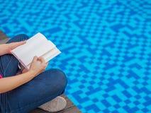 Frauenlesung und entspannender naher Luxusswimmingpool stockfoto