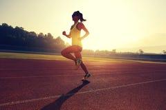 Frauenläufer, der auf Stadionsbahn läuft Lizenzfreie Stockbilder