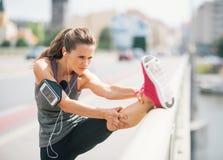 Frauenläufer, der Bein auf Schiene im Sommer in der städtischen Landschaft ausdehnt Stockbilder