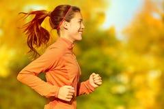 Frauenläufer, der in Fallherbstwald läuft Stockfoto