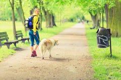 Frauenläufer, der mit Hund im Sommerpark geht Lizenzfreie Stockfotos