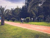 Frauenm?dchen, das ein Fahrrad auf die Gasse mit gr?nen Palmen im Park auf einem tropischen warmen Sommerurlaubsort reitet lizenzfreies stockfoto