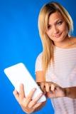 Frauenmädchen, das Tablettenberührungsflächenlesungs-eBook Eleser auf Blau verwendet Lizenzfreie Stockfotografie