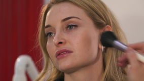 Frauenmake-upkünstler, der das blonde Mädchen des Makes-up verwendet Bürsten tut stock video footage
