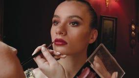 Frauenmake-upk?nstler malt Lippen eines sch?nen jungen M?dchens Fotomodell bereitet sich f?r eine Fotosession vor stock video