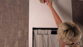 Frauenmalerei über einem Fenster mit einem Malerpinsel stock video footage