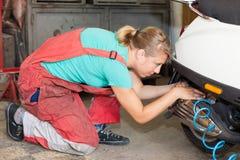 Frauenmechaniker, der einen Reifen auf einem Bewegungsfahrrad pumpt Lizenzfreie Stockfotos