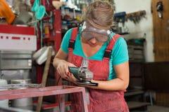 Frauenmechaniker, der einen Winkelschleifer verwendet Lizenzfreie Stockfotografie