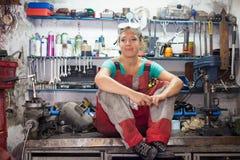 Frauenmechaniker, der in einer Werkstatt aufwirft Stockfoto
