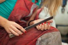 Frauenmechaniker, der ihre Nägel mit großer Metalldatei archiviert Lizenzfreie Stockbilder