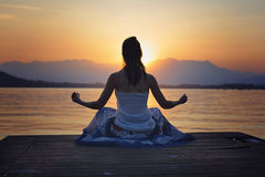 Frauenmeditation vor goldenem Sonnenuntergang lizenzfreie stockfotografie