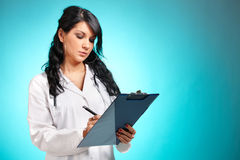 Frauenmedizindoktor mit Feder und Notizblock Stockfoto