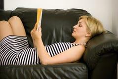 Frauenmesswert auf Couch Stockfoto