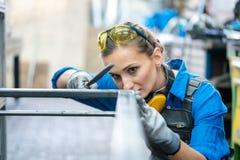 Frauenmetallarbeiter, der die Genauigkeit ihrer Arbeit überprüft lizenzfreies stockfoto