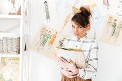 Frauenmodedesigner, der Sketchbook bei der Stellung an ihrem Studio hält stockfoto