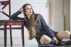 Frauenmodell im Kleid mit modernen Stiefeln und den hellen roten Lippen Stockbild