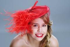 Frauenmodeporträt im roten Weinlesehut mit Federn Stockfotografie