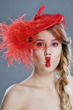 Frauenmodeporträt im roten Weinlesehut mit Federn Lizenzfreies Stockfoto