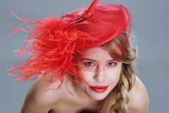 Frauenmodeporträt im roten Weinlesehut mit Federn Stockfoto
