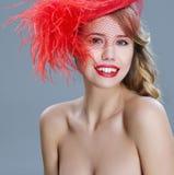 Frauenmodeporträt im roten Weinlesehut mit Federn Stockfotos