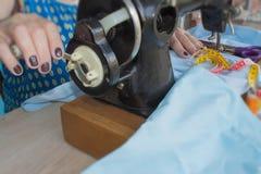 Frauennäherinsitzen und näht auf Nähmaschine Damenschneiderinarbeit über die Nähmaschine Schneider, der ein Kleid in ihrem workpl Lizenzfreies Stockbild