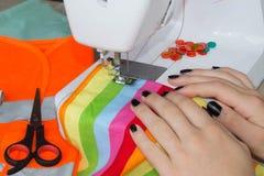 Frauennäherinsitzen und näht auf Nähmaschine Damenschneiderinarbeit über die Nähmaschine Schneider, der ein Kleid in ihrem workpl Stockfotografie