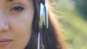 Frauennahaufnahme in hörender Musik der Kopfhörer Traurige Melodie und Traurigkeit in den Augen stock video footage