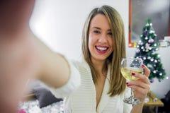 Frauennehmen selfie am Telefon mit dem Weihnachtsbaum-Griffglas der Rebe, neues Jahr feiernd Weihnachtsniederlassung und -glocken stockfoto