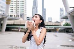Frauenniesen auf Straße weil Verschmutzung, junge weibliche erhaltene Nasenallergie lizenzfreie stockfotografie