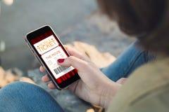 Frauennote der Schirm ihres Smartphone mit digitalem Tic des Kinos stockfoto