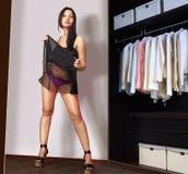 Frauenpaßsitze auf einer schwarzen Kleidinspektion Stockfotos
