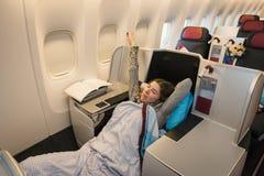 Frauenpassagier, der an der Business-Class des Flugzeuges schläft lizenzfreies stockfoto