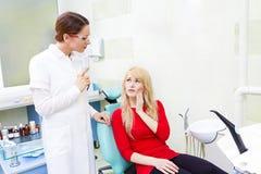 Frauenpatient im Zahnarztbüro, das Beratung von Doktor erhält stockbild