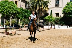 Frauenpferdereiter, der ein braunes andalusisches Pferd in historischem Ro reitet Stockbilder