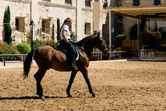 Frauenpferdereiter, der ein braunes andalusisches Pferd in historischem Ro reitet Lizenzfreie Stockfotos