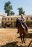 Frauenpferdereiter, der ein braunes andalusisches Pferd in historischem Ro reitet Lizenzfreie Stockbilder