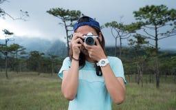Frauenphotograph, der ein Foto im Kiefernwald auf Reise vacat macht Stockfotografie